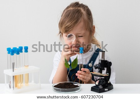Little girl is behind the desk. Microscope and the tree are near her. Chemistry class. E-learning. Stem education.