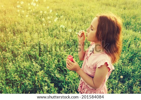 Little girl is blowing a soap bubbles in summer meadow. With instagram filter.