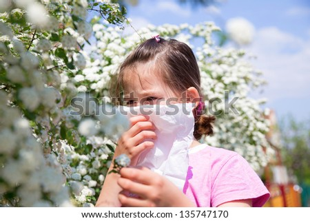 Little girl is blowing her nose - stock photo