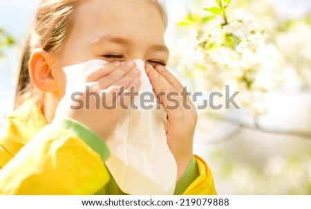 Little girl is blowing her nose near spring tree in bloom