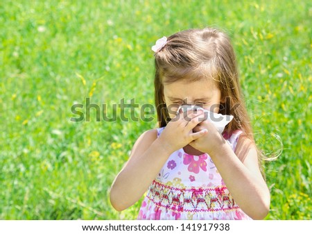 Little girl is blowing her nose on green meadow - stock photo