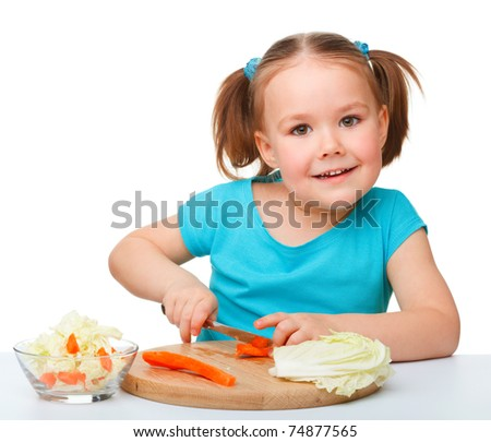 Little girl is cutting carrot for salad using kitchen knife, isolated over white - stock photo