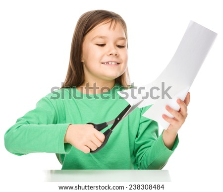 Little girl is cutting paper using scissors while sitting at table, isolated over white - stock photo