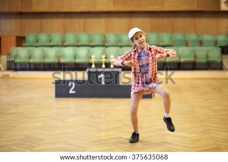 Little girl is dancing in hall near podium. - stock photo