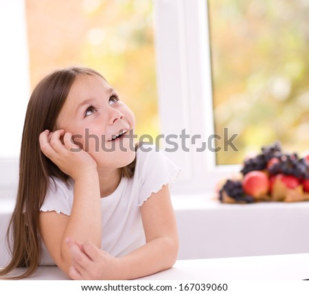 Little girl is daydreaming while sitting at table - stock photo