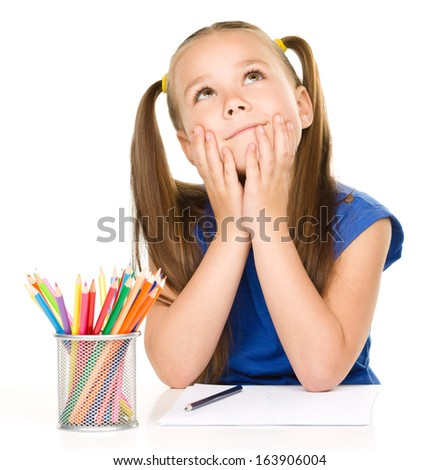 Little girl is daydreaming while sitting at table and drawing with color pencils, isolated over white - stock photo