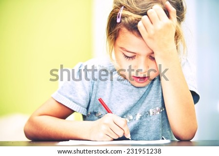 Little girl is doing his homework for elementary school. - stock photo