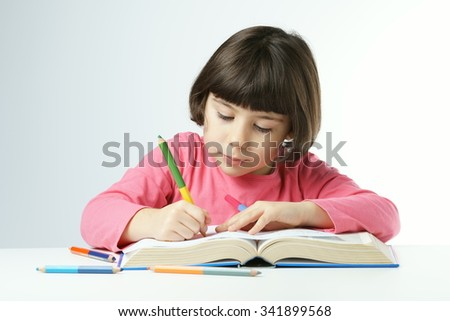 little girl is doing homework on a white background, dressing a pink shirt