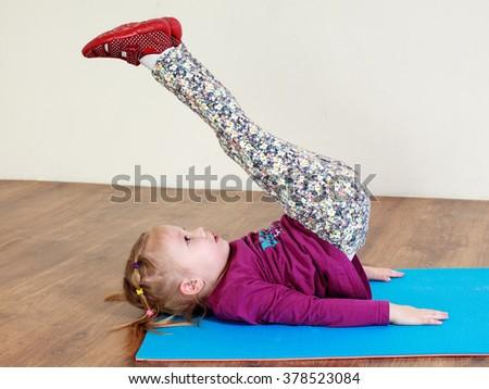 Little girl is doing leg lifting workout on a mat - stock photo