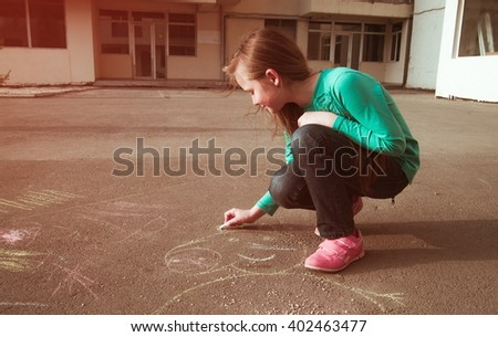 little girl is drawing outdoors