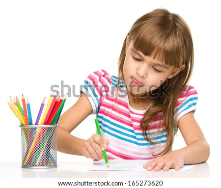 Little girl is drawing using color pencils while sitting at table and sticking her tongue out, isolated over white - stock photo