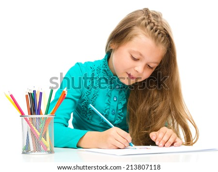 Little girl is drawing using color pencils while sitting at table, isolated over white