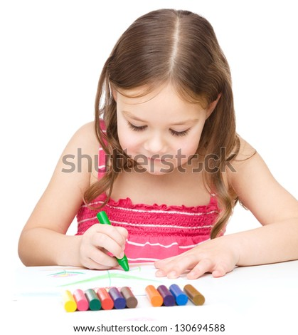 Little girl is drawing using colorful crayons while sitting at table, isolated over white - stock photo