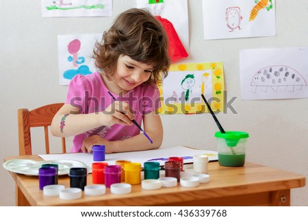 Little girl is drawing with paints and paintbrush. - stock photo