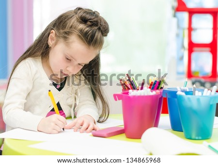 Little girl is drawing with pen in preschool - stock photo
