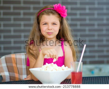 Little girl is drinking cherry juice and eating popcorn while sitting on terrace - stock photo