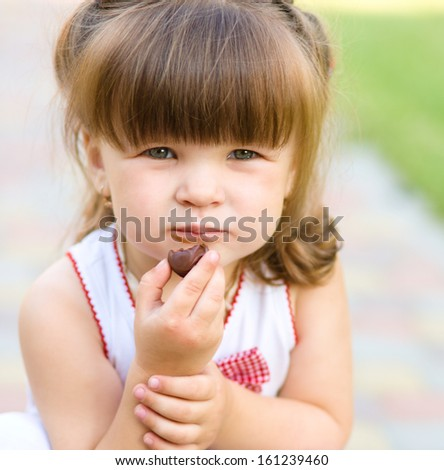 Little girl is eating chocolate candy, outdoor shoot - stock photo