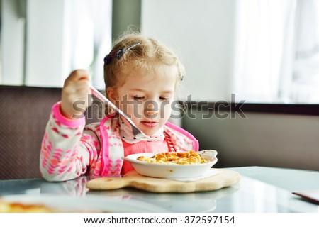 little  girl is eating in the restaurant - stock photo