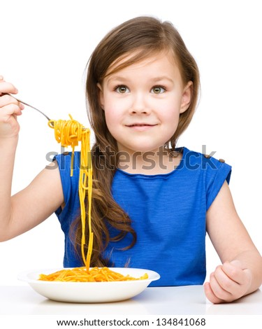 Little girl is eating spaghetti, isolated over white - stock photo