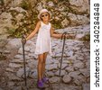 Little girl is engaged in Nordic Walking in the mountains of Croatia - in the Great Paklenica. - stock photo