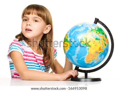 Little girl is examining globe while sitting at table, isolated over white