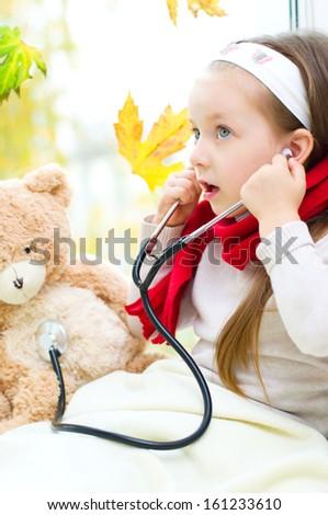 Little girl is examining her teddy bear using stethoscope - stock photo