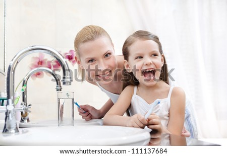 Little girl is going to brush her teeth with her mother - stock photo