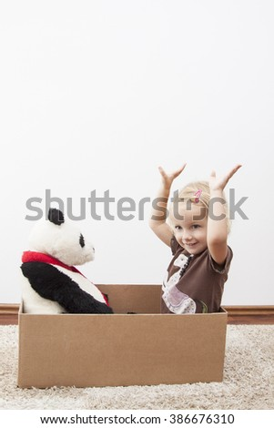 little girl is happy to move, with panda bear on cardbox - stock photo