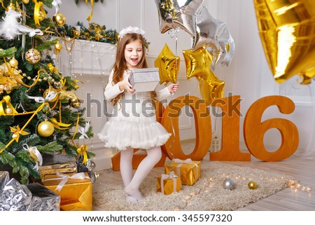 Little girl is happy with gifts for New Year 2016. Girl holding a box. Holiday and fun. Merry Christmas. - stock photo