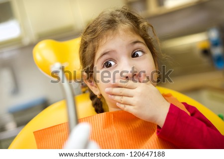 Little girl is having her teeth checked by dentist - stock photo