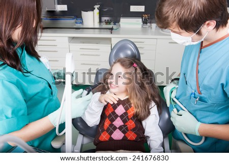 Little girl is having her teeth examined by dentist.Little girl sitting and smiling in the dentists office. Child not afraid of dentist - stock photo