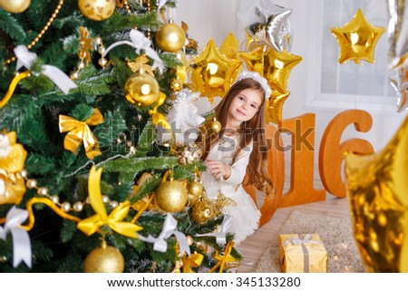 Little girl is hiding and peeking out of a Christmas tree. New Year 2016 holiday and fun. - stock photo