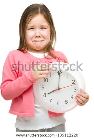 Little girl is holding big clock and showing unhappy grimace, isolated over white - stock photo