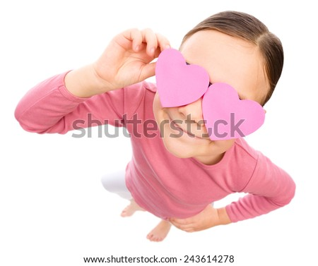 Little girl is holding hearts over her eyes, fisheye portrait, valentine concept, isolated on white - stock photo