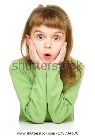 Little girl is holding her face in astonishment, isolated over white - stock photo