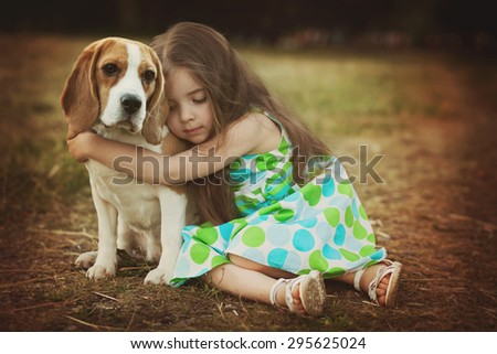 little girl is hugging  dog outdoors - stock photo