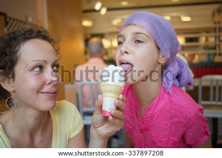 Little girl is licking ice-cream in her mothers hand. - stock photo