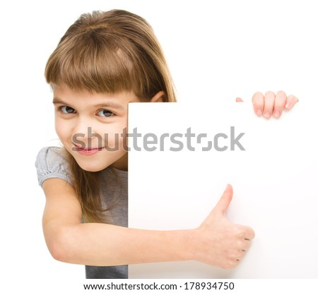 Little girl is looking out from the blank banner and showing thumb up sign, isolated over white - stock photo