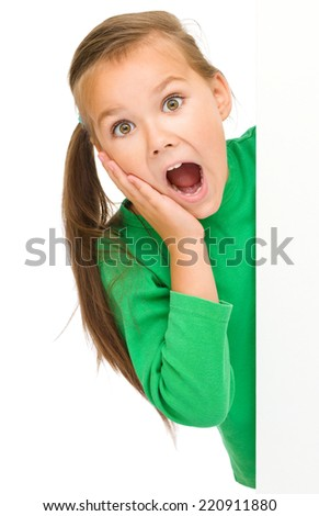 Little girl is looking out from the blank banner, holding her face in astonishment, isolated over white - stock photo