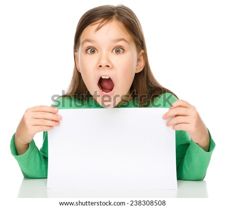 Little girl is looking out from the blank banner, opening her mouth in astonishment, isolated over white - stock photo