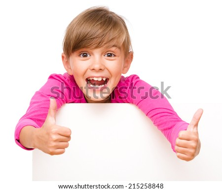Little girl is looking out from the blank banner showing thumb up sign, isolated over white - stock photo