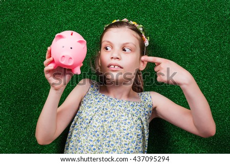 Little girl is lying on artificial grass and pointing at piggy bank. - stock photo