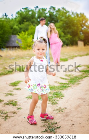 little girl is on the road in the background of the parents