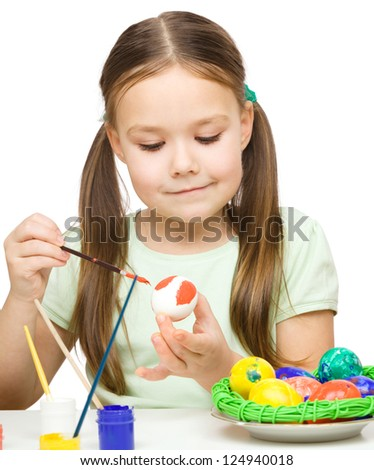 Little girl is painting eggs preparing for Easter, isolated over white - stock photo