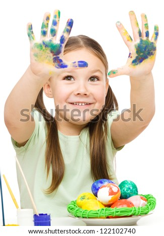 Little girl is painting eggs preparing for Easter showing her hands, isolated over white - stock photo