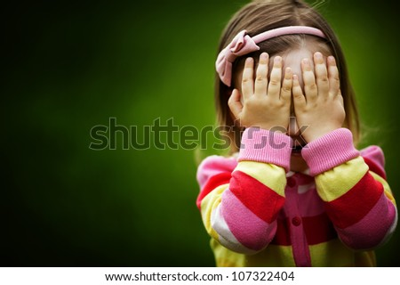 little girl is playing hide-and-seek hiding face - stock photo