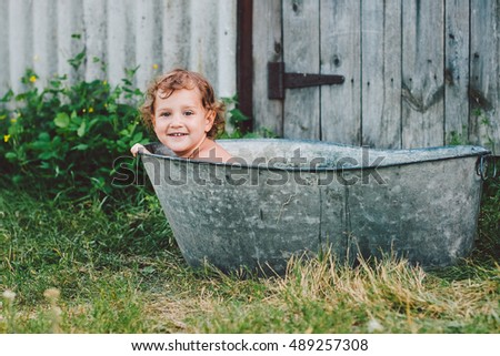 Little girl is playing in a bath outdoor