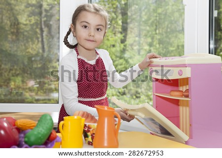 Little girl is playing in her toy kitchen