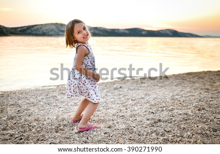 Little girl is playing on sandy beach in sunset or sunrise. Child in white dress is enjoying a day near the sea ocean. - stock photo