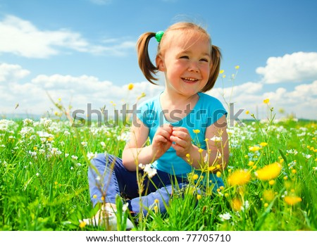 Little girl is playing while sitting on green meadow